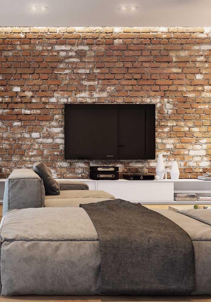 Nessa sala de estar, os tijolinhos de demolição realçam a parede da TV