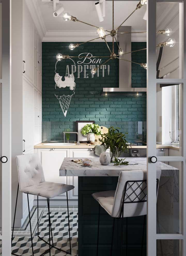 O verde musgo da parede de tijolinhos é o grande destaque dessa cozinha branca