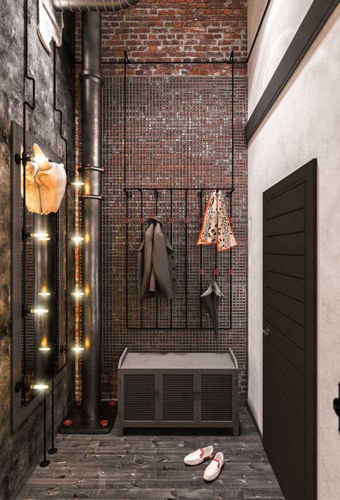 O hall de entrada moderno e industrial não podia contar com outro revestimento que não fosse o de tijolinhos