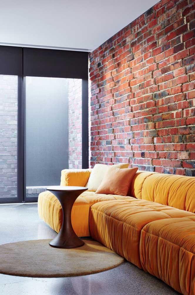 O sofá amarelo reforça o aspecto acolhedor e aconchegante da parede de tijolinhos