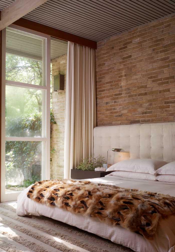 O quarto de casal com pé direito alto traz uma parede de tijolinhos à vista que se estende até a varanda