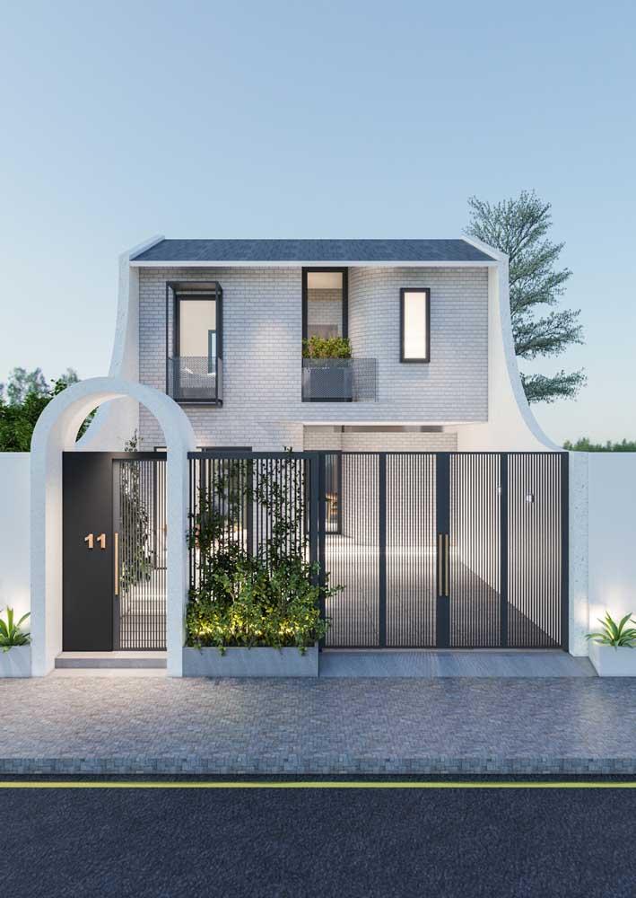 Fachada de casa moderna feita com tijolinhos à vista; a cor branca usada no material contraste perfeitamente com os detalhes em preto