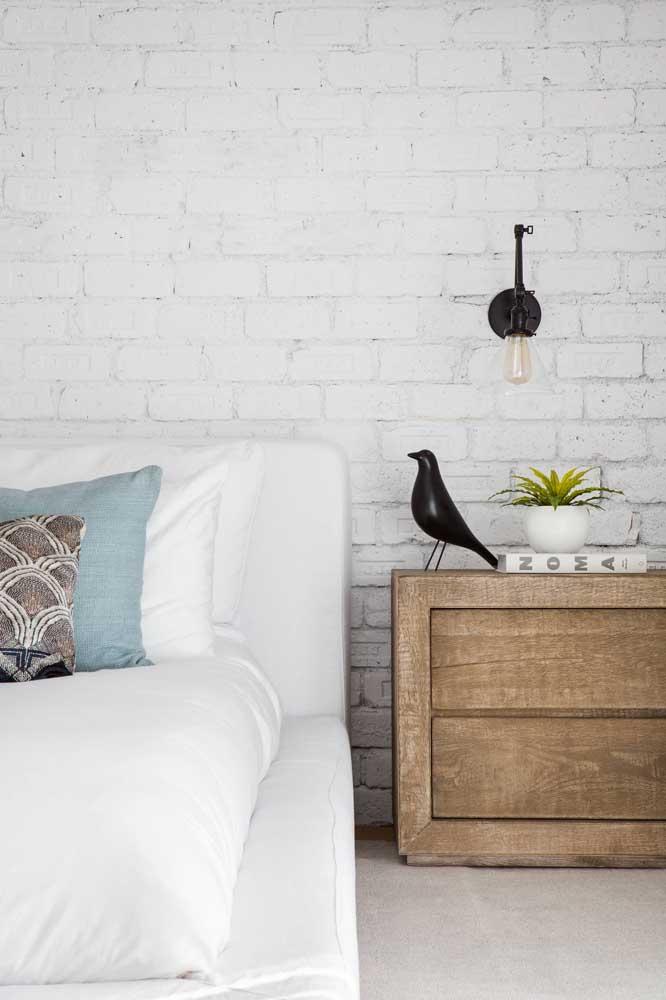 A parede de tijolos de demolição na cor branca confere um visual despojado, mas ainda assim, muito charmoso para o quarto