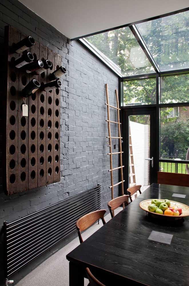 Essa sala de jantar integrada à área externa da casa investiu em uma parede de tijolinhos escuros