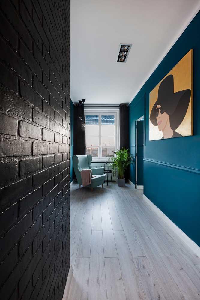 A casa moderna e jovial apostou em uma parede de tijolinhos à vista na cor preta em contraste com o azul do restante do ambiente