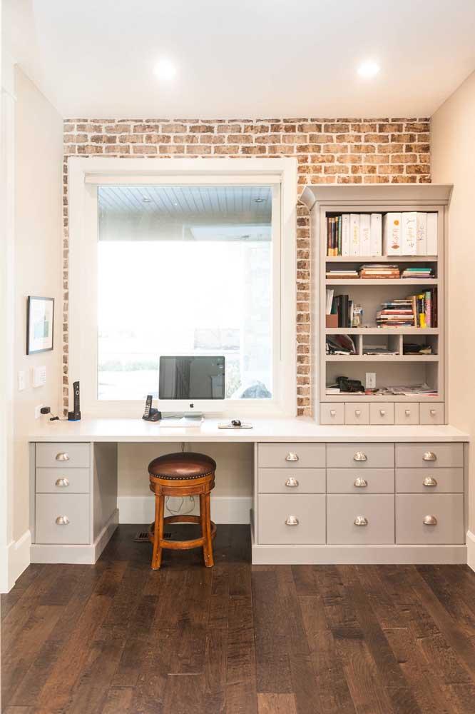 O home office branco e clássico contou com a modernidade e o despojamento dos tijolinhos à vista