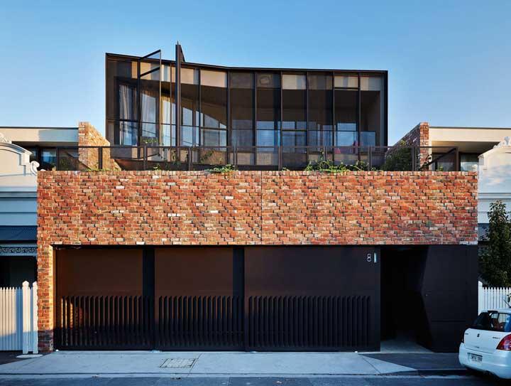 Fachada de casa moderna revestida com tijolinhos à vista