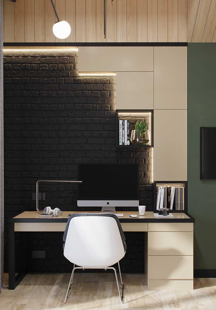 O home office fica moderno e despojado com a parede de tijolinhos à vista na cor preta