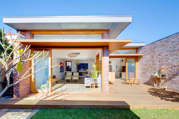 Fachada de tijolinhos à vista complementada pelo uso da madeira