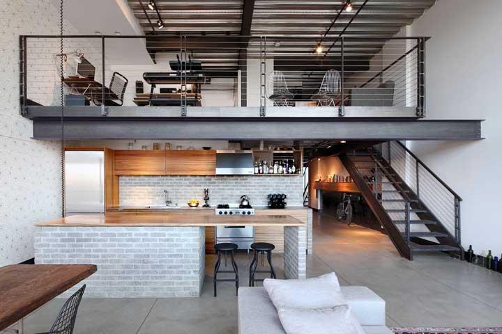 Nessa casa ampla com mezanino, os tijolinhos à vista foram usados para revestir a parede lateral se estendendo por toda a altura do pé direito