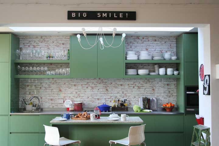 O tom verde suave dos armários encaixou como uma luva na parede de tijolinhos à vista com acabamento em pátina