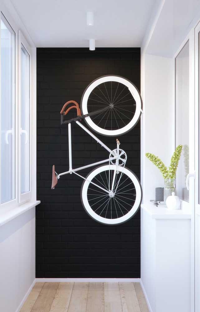 Aqui, a parede de tijolinhos preta serve para destacar uma parte especial do ambiente, nesse caso, o local onde a bicicleta é guardada