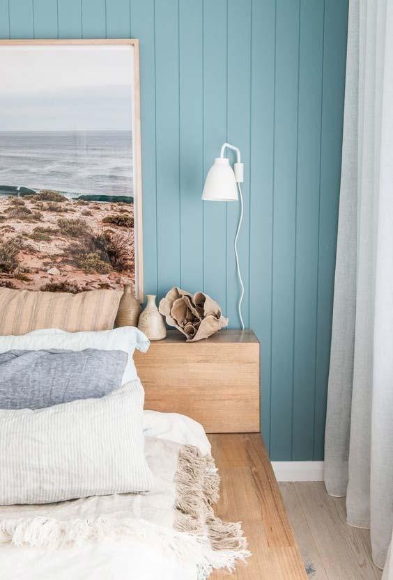 cama baixa com estrutura em madeira e uma decoração todinha inspirada no mar