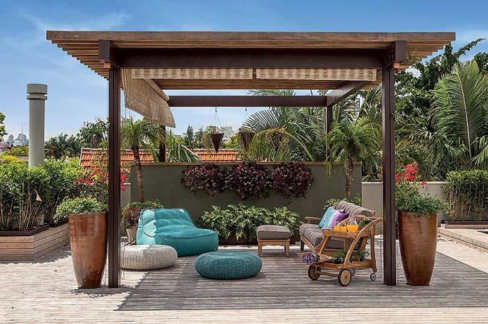 O pergolado com persianas laterais traz sombra e garante a beleza desse jardim