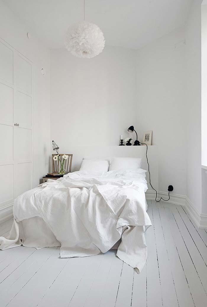 Quarto branco com piso de madeira