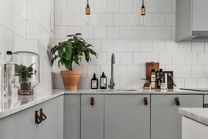Puxadores de tiras de couro e vaso invertido decoram a cozinha com personalidade