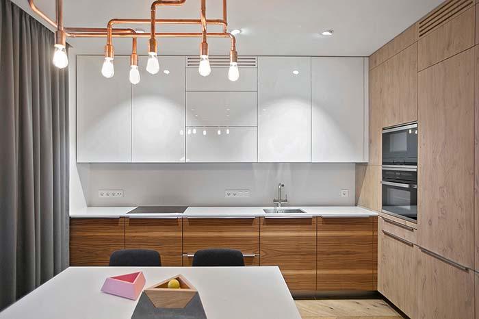 Cortina cinza em combinação com o estofado das cadeiras; luminária de cobre traz sofisticação e modernidade à cozinha