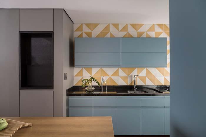 Revestimento amarelo e branco decora a cozinha junto do armário azul