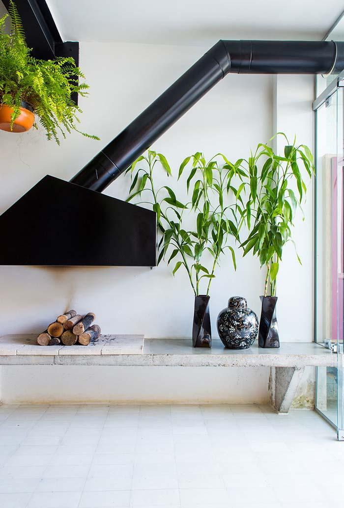 Ambiente planejado com lareira rústica na pedra e coifa de metal