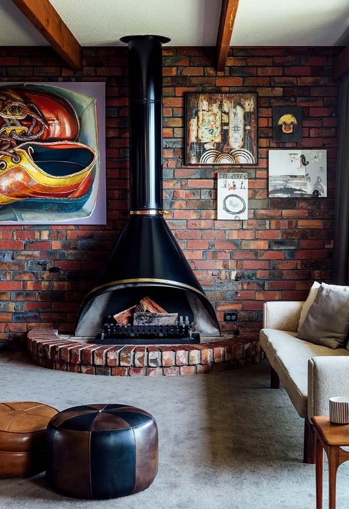 Sala num estilo industrial com tijolos aparente e lareira com estrutura de metal