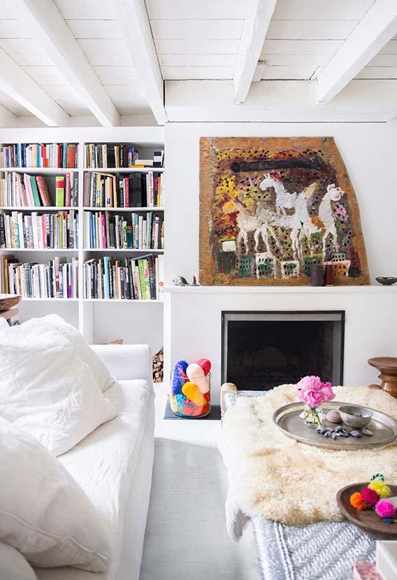 Uma obra apoiada na parte superior da lareira ajuda a dar personalidade para o ambiente