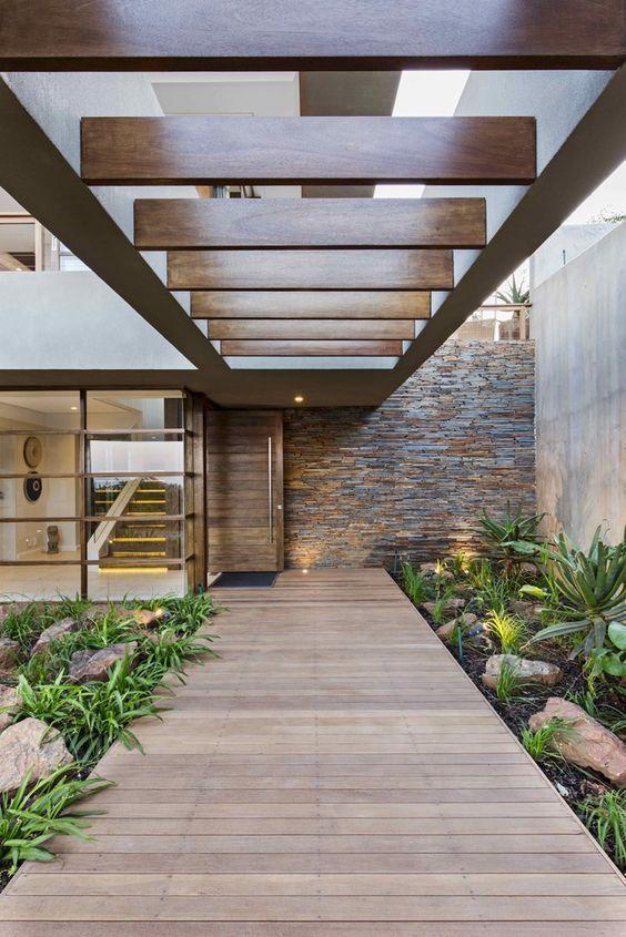 Corredor sob o pergolado de madeira: estrutura dá acesso à área interna.