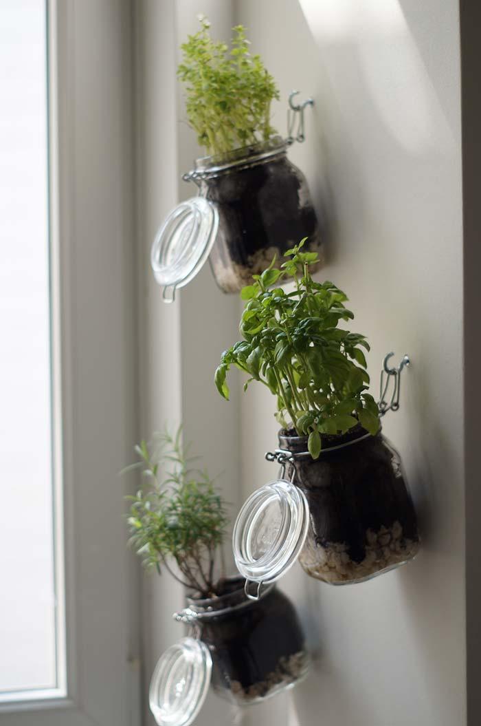 Ganchinhos na parede seguram os potinhos de vidro com ervas