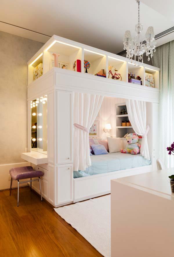 Cama planejada com armários e nichos no quarto infantil feminino
