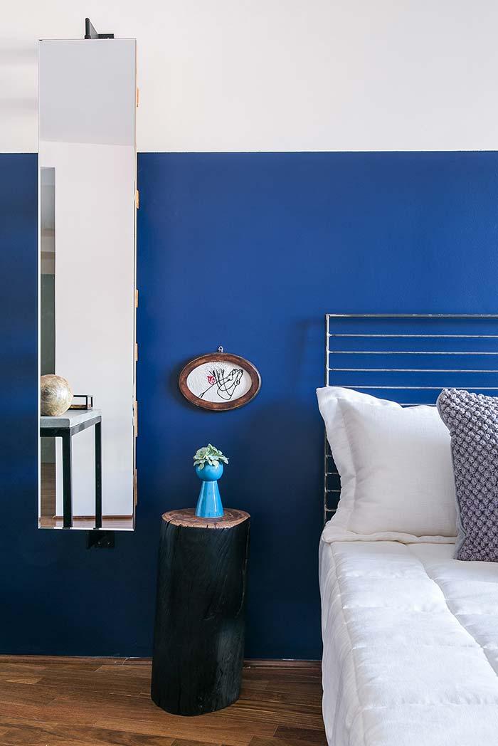 Espelho vertical alongado quebra o azul intenso da parede