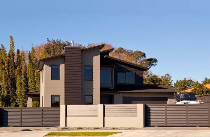Portão marrom na cor e no desenho da fachada