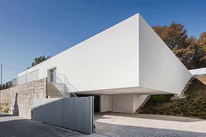 Muro de pedras e portão de alumínio branco