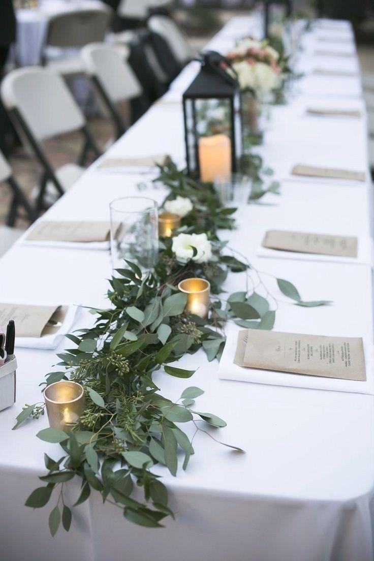 Mesa única decorada com arranjo de folhas em casamento barato