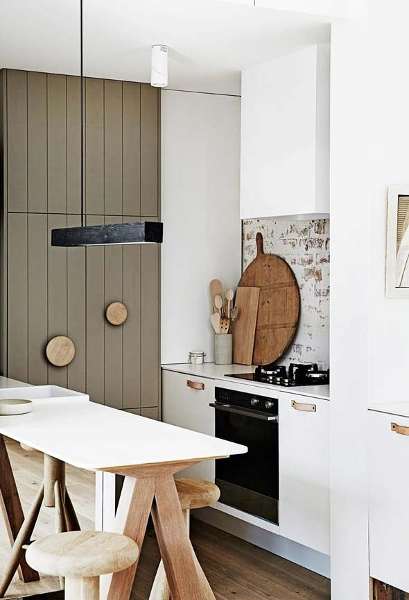 Mesa de madeira no centro da decoração desta cozinha pequena