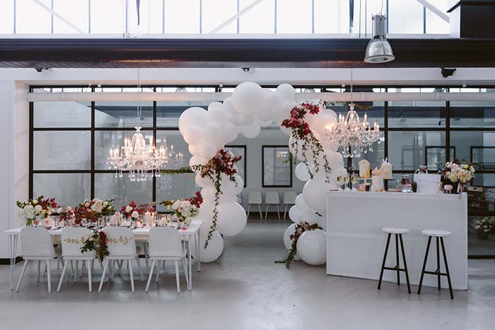 Arco descontruído de balões recepciona os convidados na entrada da festa