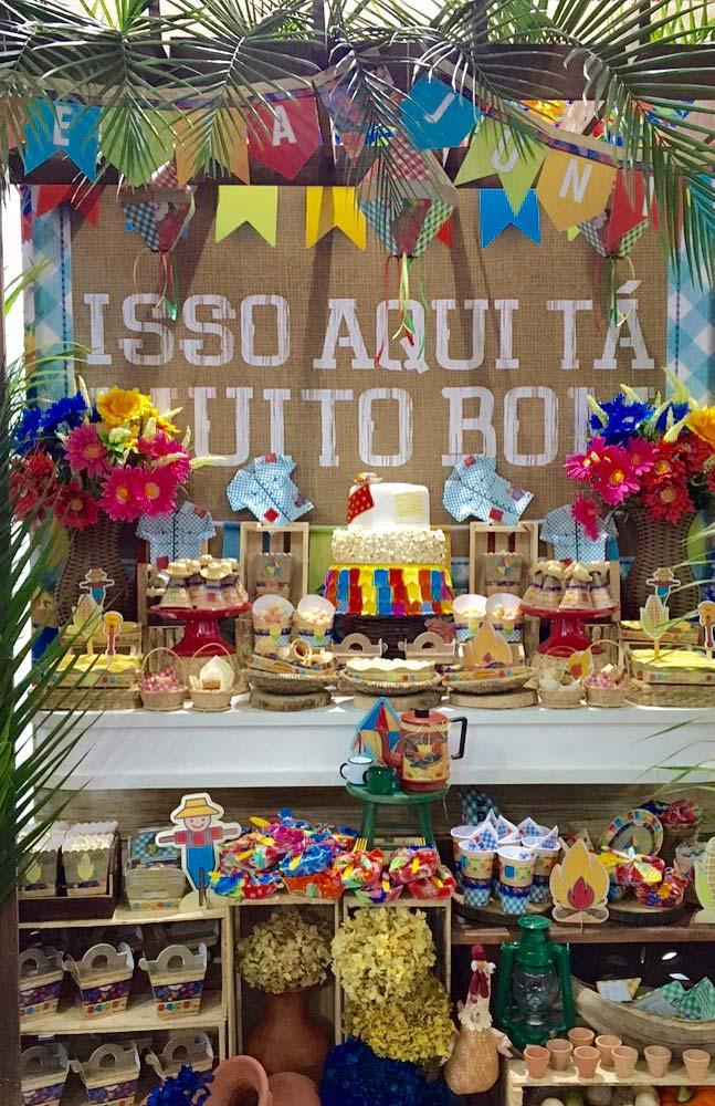 Painel de festa junina com folhas de palmeira e bandeirinhas