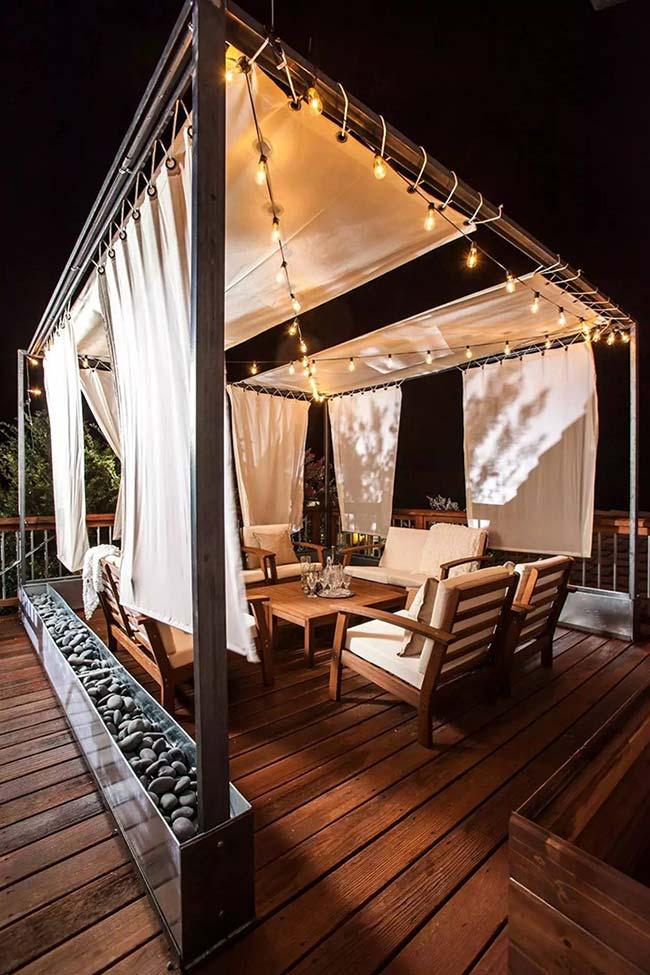 As cortinas do pergolado trouxeram mais privacidade a varanda de madeira