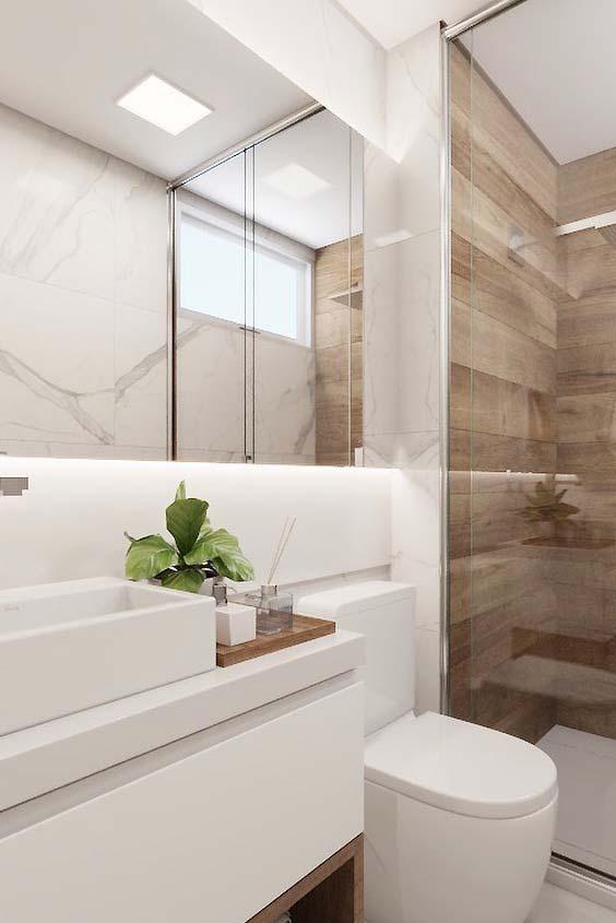 Detalhes em madeira valorizam o banheiro branco