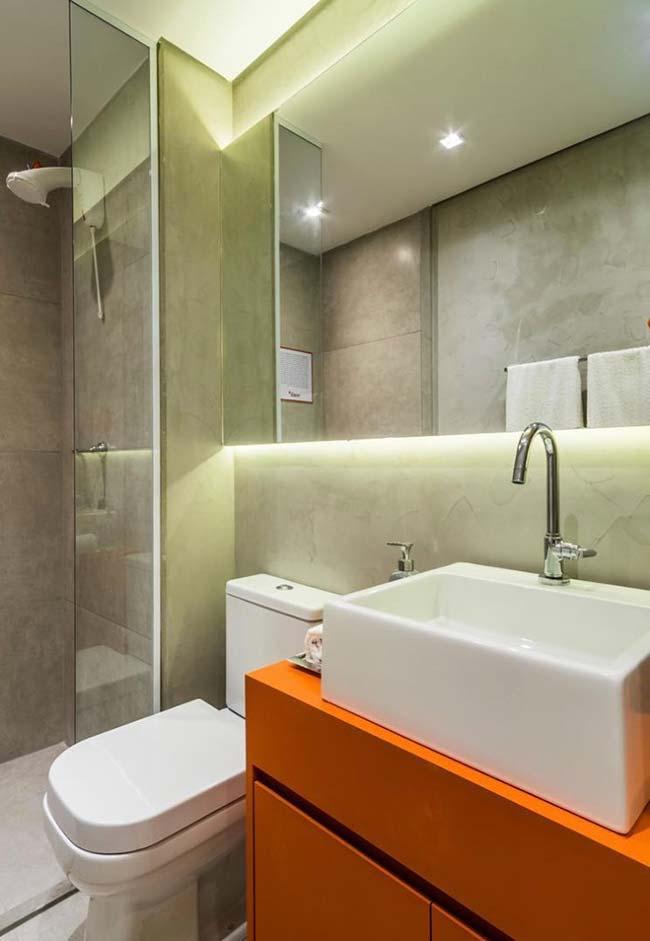 O gabinete laranja dá cor e vida para o banheiro de cor sóbria