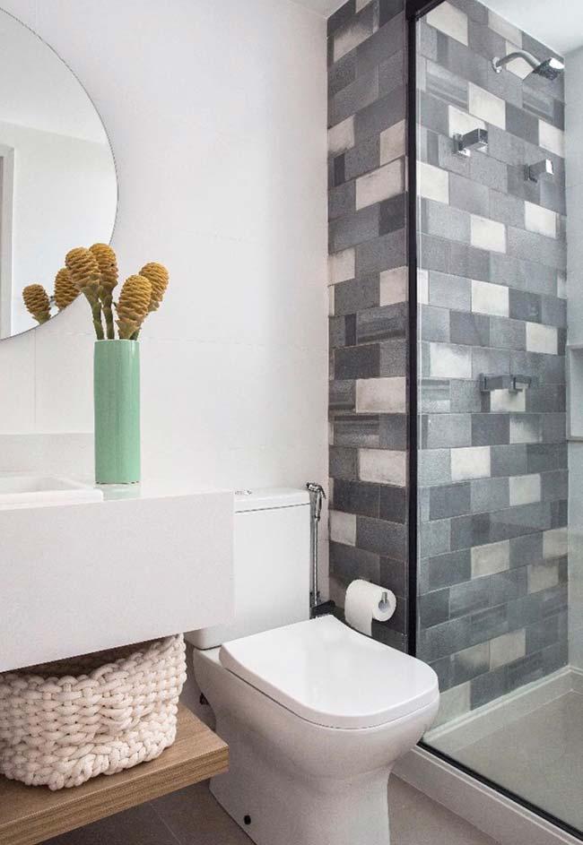 Box de azulejos azuis e cinza contrastam harmoniosamente com o restante do banheiro branco