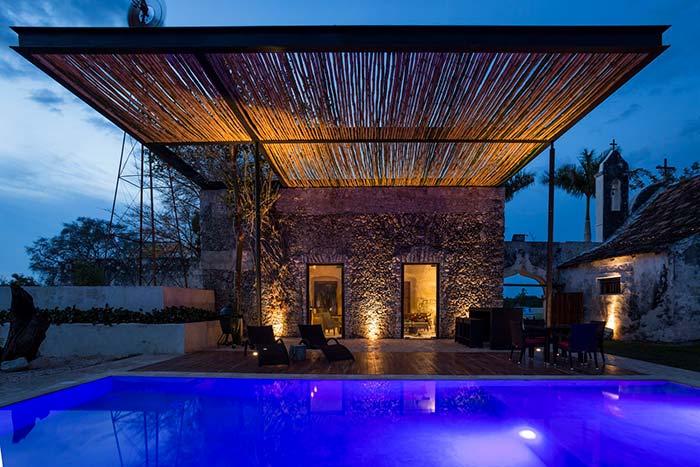 Pergolado de bambu cobrindo a piscina da casa de fazenda