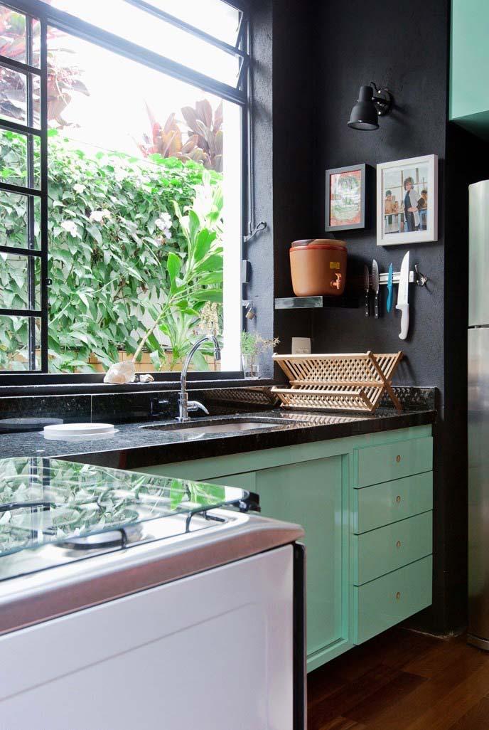 Parede preta e granito Verde Ubatuba na bancada da cozinha