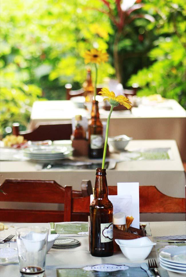 Arranjo de mesa com flor em garrafa de cerveja