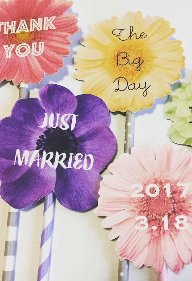 Flores variadas fazem o fundo dessas plaquinhas para festa de casamento