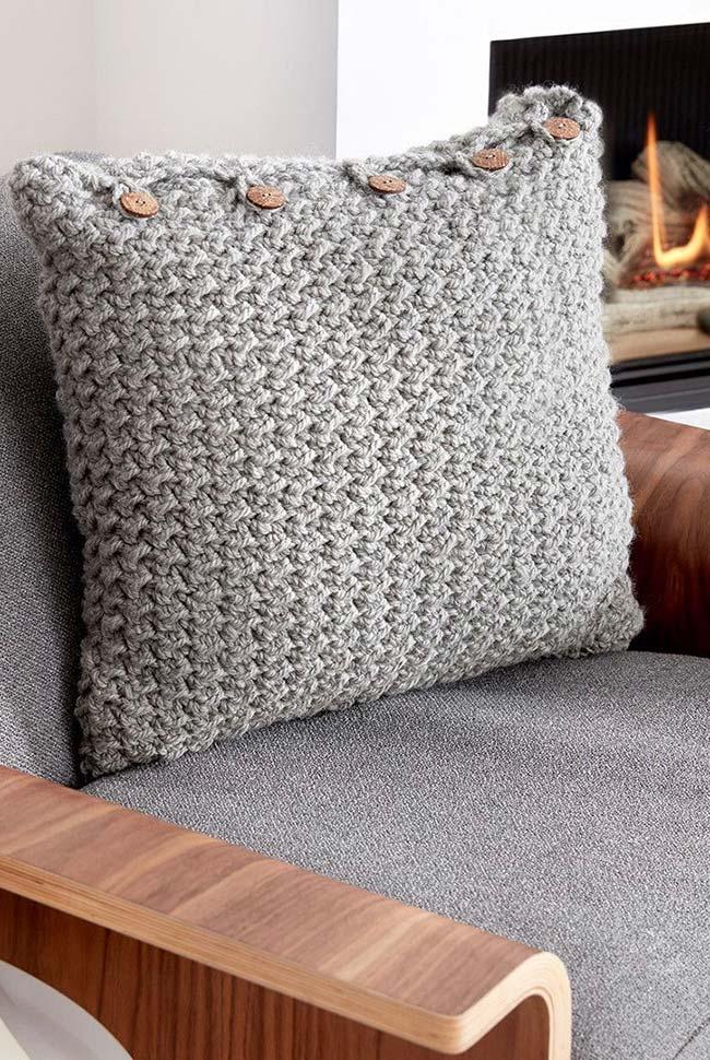 Botões de madeira na capa de almofada de crochê