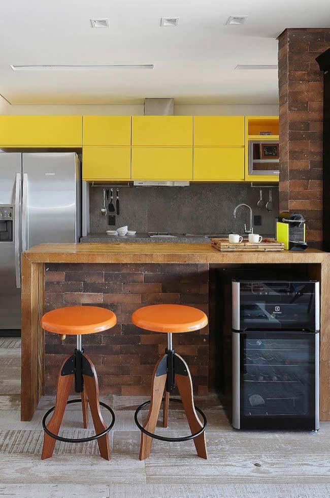 Cores quentes em combinação com a bancada de madeira nessa cozinha