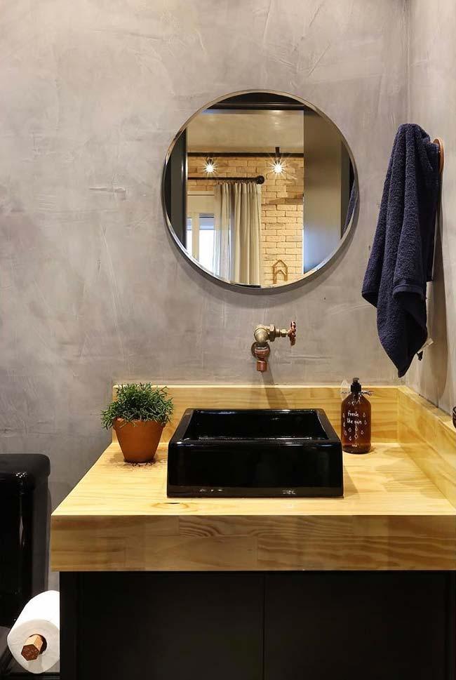 Bancada de madeira no banheiro e parede com cimento queimado