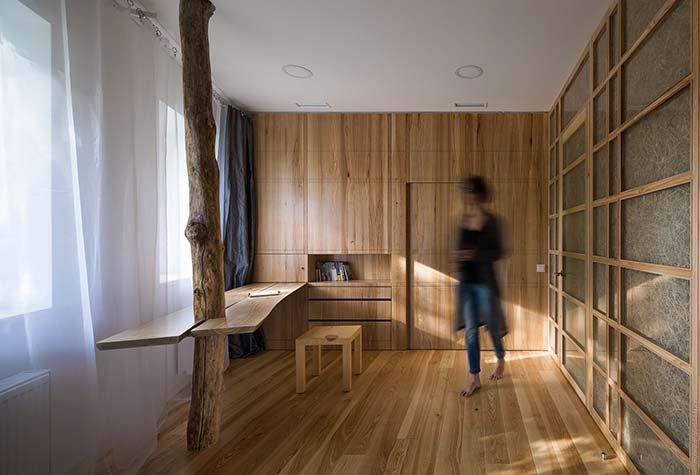 Tronco de árvore na sala com bancada de madeira