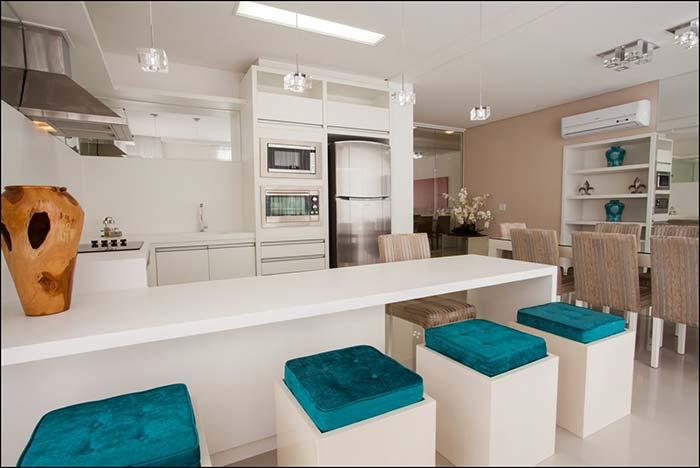 Espaço gourmet branco e azul; no lugar de banquetas, os pufes confortáveis na altura da bancada