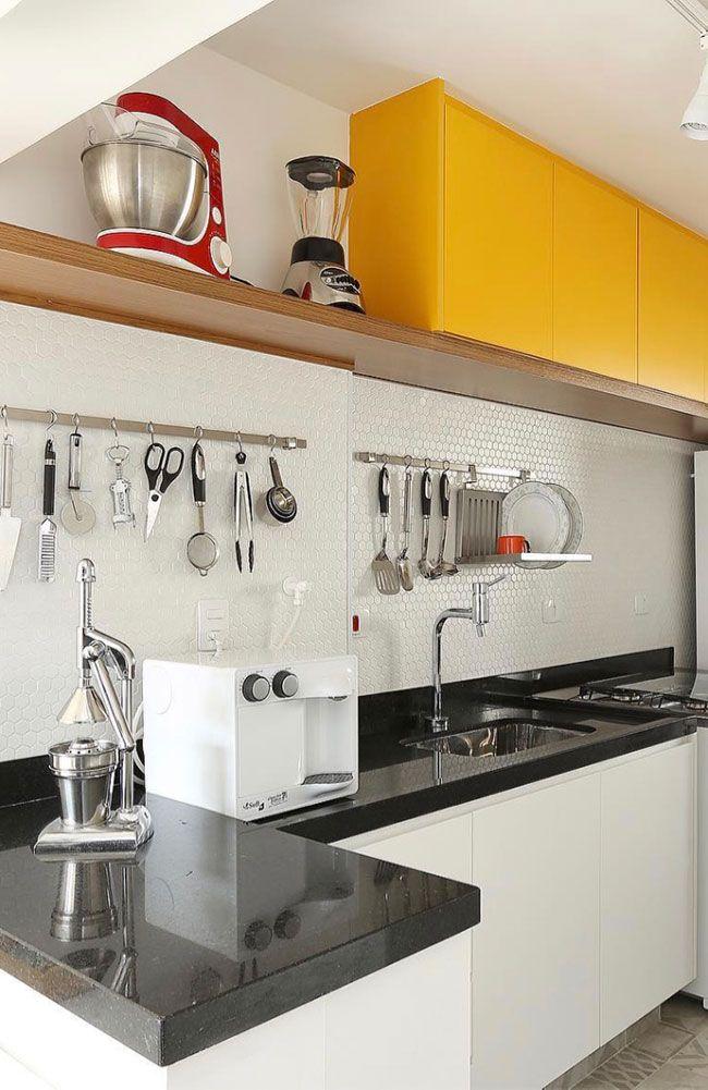 Móvel branco com pedra preta nesse projeto de cozinha