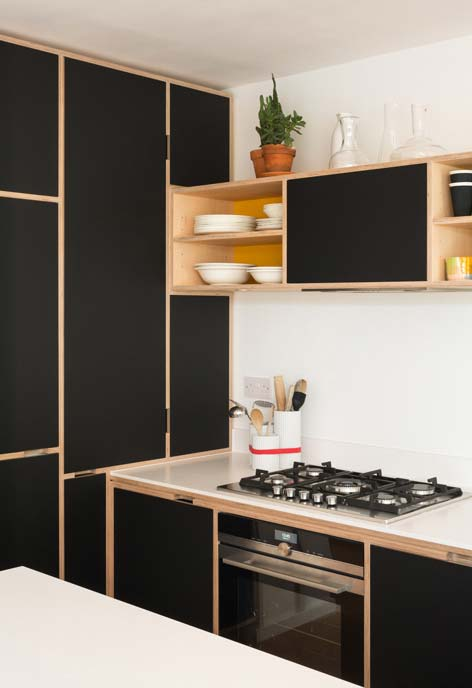 Preto dessa cozinha é recortado pelos detalhes em madeira crua